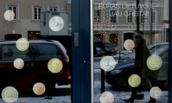 """A pedestrian is reflected in a window decorated with Lithuanian promo Euro coins with inscription """"The euro is coming soon to Lithuania """" in Vilnius, Lithuania, Monday, Dec. 29, 2014. Political leaders are hoping that joining the euro on Jan. 1 will help Lithuania distance itself further from Russian influence and reduce government borrowing costs. (AP Photo / Mindaugas Kulbis)"""