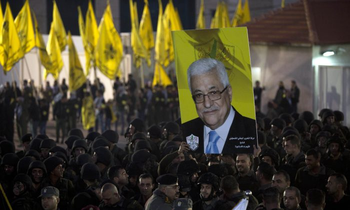 Palestinians hold up a poster showing President Mahmoud Abbas, as they celebrate the 50th anniversary of the Fatah movement in the West Bank city of Ramallah, Wednesday, Dec. 31, 2014. (AP Photo/Majdi Mohammed)