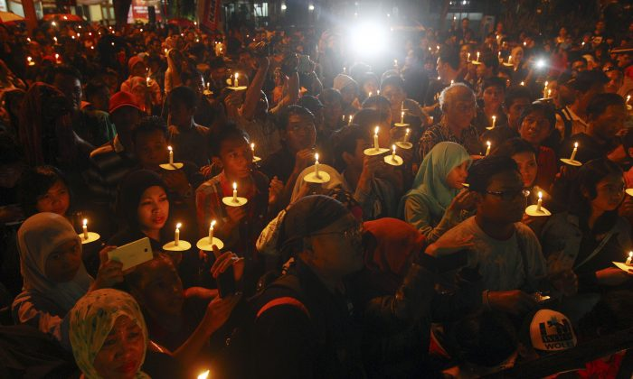 Indonesians hold candles to pray for the victims of AirAsia Flight 8501 in Surabaya, Indonesia, Wednesday, Dec. 31, 2014. Bad weather hindered efforts to recover victims of the jetliner on Wednesday, and sent wreckage drifting far from the crash site, as grieving relatives prayed for strength to endure their losses. (AP Photo/Firdia Lisnawati)