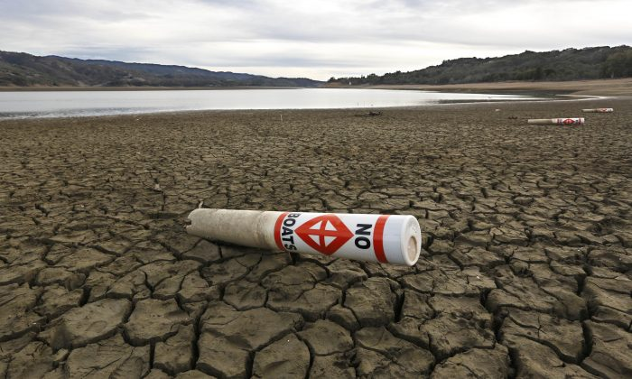 FILE- In this Feb. 4, 2014 file photo, a warning buoy sits on the dry, cracked bed of Lake Mendocino near Ukiah, Calif. New laws to deal with California's historic drought are among the more than 900 bills passed by the Legislature and signed by California Gov. Jerry Brown in 2014, that will take effect Jan. 1, 2015. (AP Photo/Rich Pedroncelli, File)