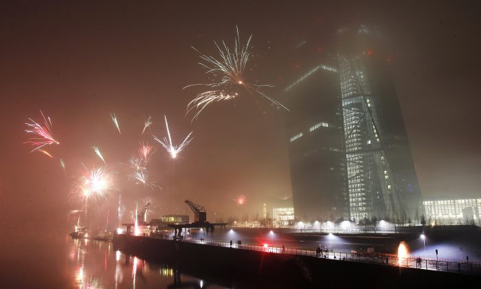 Fireworks explode during New Years celebrations near the new headquarters of the European Central Bank in Frankfurt, Germany, Thursday, Jan. 1, 2015. (AP Photo/Michael Probst)