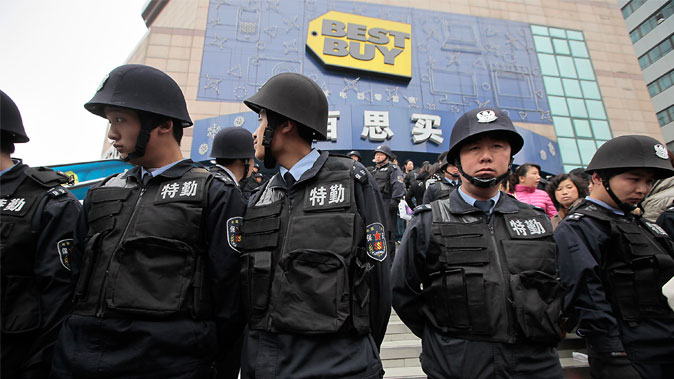 Security guard personnel stand guard as people line up to complain or seek help with customer service outside a Best Buy outlet store in Shanghai on Feb. 25, 2011. (AP Photo/Eugene Hoshiko)