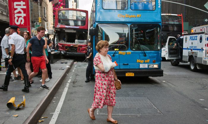 A woman, her arm bandaged and in a sling, after being treated at the scene of a traffic accident in New York City's Theater District on Tuesday Aug. 5, 2014. The number of pedestrians killed by cars in New Jersey spiked in 2014, throwing 2013's record low figure into reverse. (AP Photo/Bebeto Matthews)