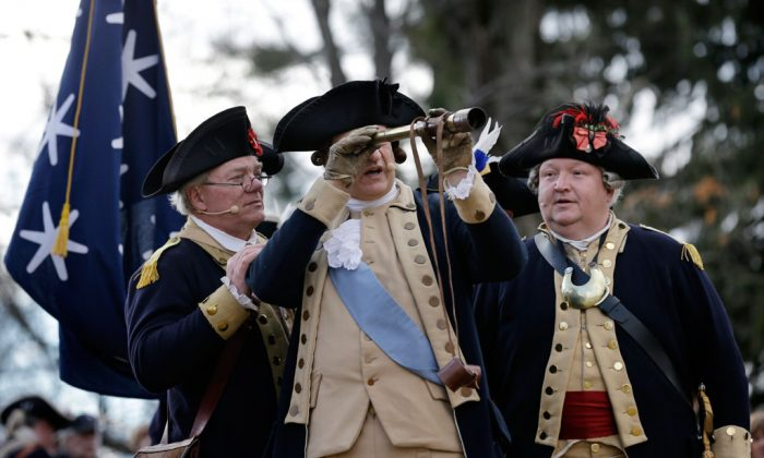 George Washington (C), played by John Godzieba, looks toward New Jersey through a scope during the 62nd annual reenactment of Washington's daring Christmas 1776 crossing of the river - the trek that turned the tide of the Revolutionary War, on Thursday, Dec. 25, 2014, in Washington Crossing, Pa. (AP Photo/Mel Evans)