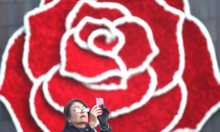 A Rose Parade spectator takes pictures while waiting the start of the 126th Rose Parade in Pasadena, Calif., Thursday, Jan. 1, 2015. (AP Photo/Ringo H.W. Chiu)