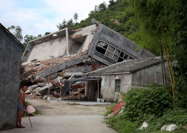 A man stands near the razed remains of a Catholic church in a village in Pingyang county of Wenzhou in eastern China's Zhejiang Province on July 16, 2014. (AP Photo/Didi Tang)