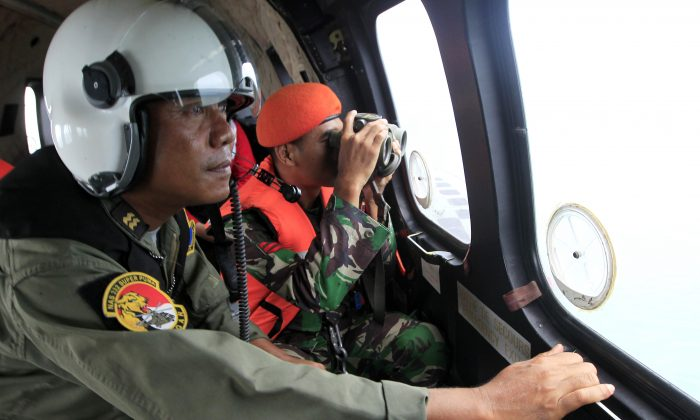 Crew members of Indonesian Air Force NAS 332 Super Puma helicopter look out of the windows during a search operation for the victims of AirAsia Flight 8501 over Kumai Bay, Indonesia, Friday, Jan. 2, 2015. (AP Photo/Bagus Indahono, Pool)