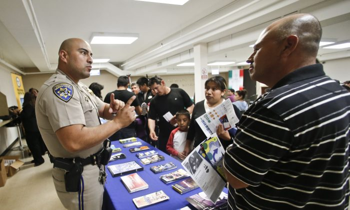 In this file photo, a California Highway Patrol officer explains to immigrants the process of getting a driver's license during an information session at the Mexican Consulate, in San Diego, Calif., on April 23, 2014. (AP Photo/Lenny Ignelzi,File)