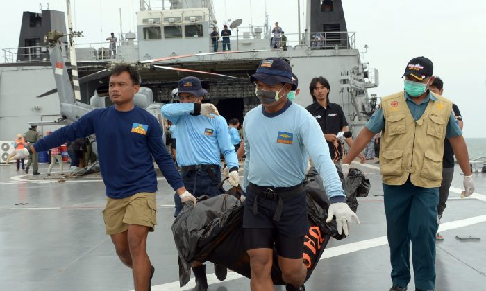 Indonesian's Navy personnel carry a bag containing a dead body of a passenger of AirAsia Flight 8501 at sea off the coast of Pangkalan Bun, Indonesia, Saturday, Jan. 3, 2015. Indonesian officials were hopeful Saturday they were honing in on the wreckage of AirAsia Flight 8501 after sonar equipment detected two large objects on the ocean floor, a full week after the plane went down in stormy weather. (AP Photo/Adek Berry, Pool)