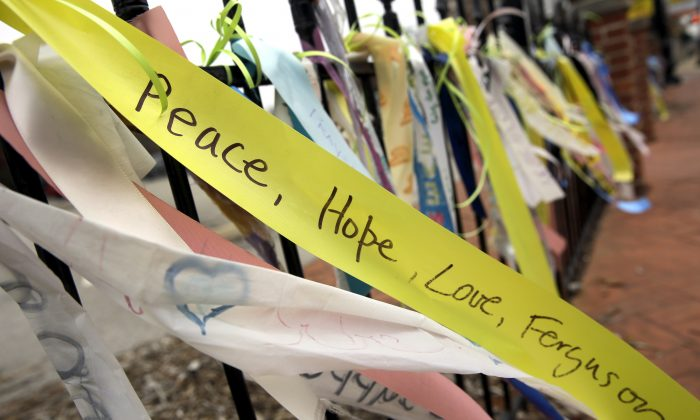 Brightly colored ribbons flutter from a wrought-iron fence along the a main thoroughfare in Ferguson, Mo., on Dec. 9, 2014. (AP Photo/Jeff Roberson)