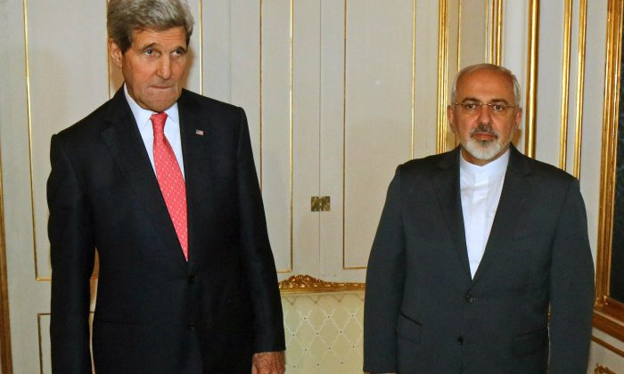U.S. Secretary of State John Kerry and Iranian Foreign Minister Mohammad Javad Zarif, right, pose for a photograph prior to a bilateral meeting of the closed-door nuclear talks in Vienna, Austria, on Nov. 23, 2014. Diplomats say Iran and the U.S. have tentatively agreed that Tehran will ship to Russia much of the material it could use to manufacture nuclear weapons. (AP Photo/Ronald Zak, Pool-File)