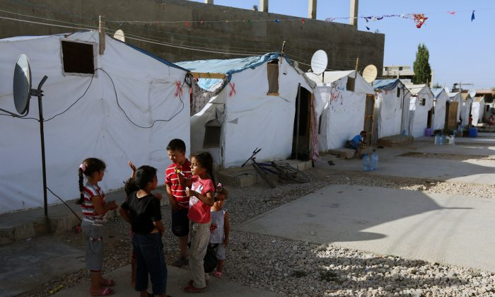 Syrian refugee children play outside their tent in a Syrian refugee camp in the eastern town of Marj, Bekaa valley, Lebanon, on June 29, 2014. The Syrian ambassador to Lebanon called on Saturday, Jan. 3, 2015, for coordination with Lebanese authorities after Beirut announced plans to impose unprecedented restrictions on Syrians trying to enter Lebanon. The move marks the most significant attempt by Lebanese authorities to stem the massive influx of an estimated 1.5 million Syrians who have sought refuge in Lebanon from the civil war raging in their homeland. (AP Photo/Bilal Hussein)