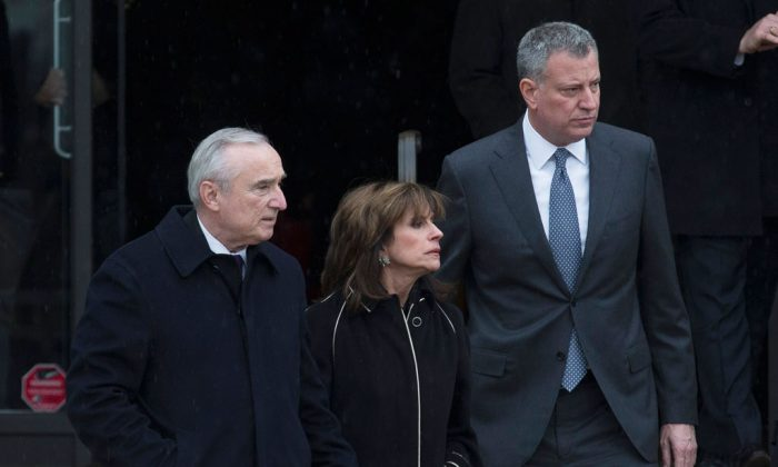 (L-R) NYPD Commissioner Bill Bratton, Rikki Klieman, Bratton's wife, and NYC Mayor Bill de Blasio, exit the wake of NYPD Officer Wenjian Liu at Aievoli Funeral Home, Saturday, Jan. 3, 2015, in the Brooklyn borough of New York. (AP Photo/John Minchillo)