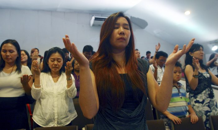 Members of Mawar Sharon church attend a prayer service for the relatives of lost loved ones aboard the AirAsia Flight 8501, in Surabaya, East Java, Indonesia Sunday, Jan. 4, 2015. About 40 members of the church were aboard the plane which crashed into the Java Sea a week ago. (AP Photo/Firdia Lisnawati)