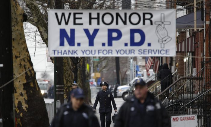 Police officers arrive to the funeral of Officer Wenjian Liu in the Brooklyn borough of New York, Sunday, Jan. 4, 2015. Liu and his partner, officer Rafael Ramos, were killed Dec. 20 as they sat in their patrol car on a Brooklyn street. The shooter, Ismaaiyl Brinsley, later killed himself. (AP Photo/Seth Wenig)