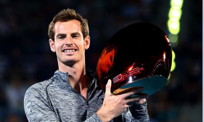 Scottish tennis player Andy Murray poses with the trophy of the Mubadala World Tennis Championship after winning the competition following the withdrawal of Serbian player Novak Djokovic from the final due to illness in Abu Dhabi, on January 3, 2015. (Marwan Naamani/AFP/Getty Images)