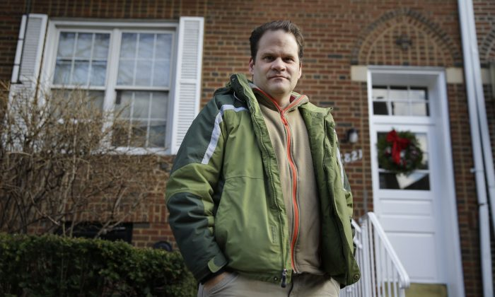 Chris Athineos poses for a picture in front of a building owned by his family in the Brooklyn borough of New York, Wednesday, Dec. 31, 2014. A looming debate in Albany could determine just how much the rent could go up for more than 2 million residents in New York City. The state laws governing the city's long-standing rent stabilization program are due to expire on June 15. (AP Photo/Seth Wenig)