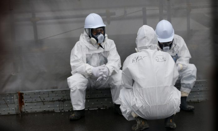 Workers wearing protective gear rest on a road at the Fukushima Dai-ichi nuclear power plant in Okuma, Fukushima Prefecture, northeastern Japan on Nov. 12, 2014. (Shizuo Kambayashi/AFP/Getty Images)