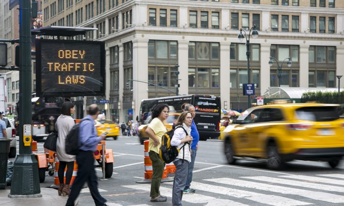 A digital board displays safety messages in front of Penn Station in Manhattan, N.Y., on Sept. 10, 2014. A law fining hit-and-run drivers in New York City has gone into effect with the New Year. (Samira Bouaou/Epoch Times)