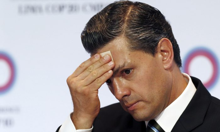 Mexico's President Enrique Pena Nieto wipes sweat from his brow during a signing ceremony among the Pacific Alliance at the Climate Change Conference in Lima, Peru, on Dec. 10, 2014. (AP Photo/Juan Karita)
