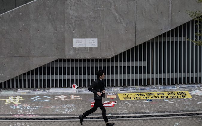 "A man runs past the ""Lennon Wall,"" an area next to the Hong Kong central government offices where pro-democracy activists wrote messages of support for the protest movement, in Hong Kong on Jan. 5, 2015."