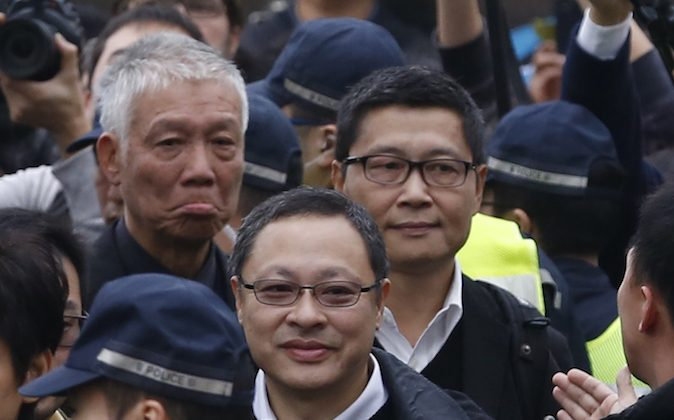 Three protest leaders, from right, Chan Kin-man, Benny Tai Yiu-ting and Chu Yiu-ming walk towards the police station in Hong Kong as they surrender to police Wed., Dec. 3, 2014. (AP Photo/Kin Cheung)
