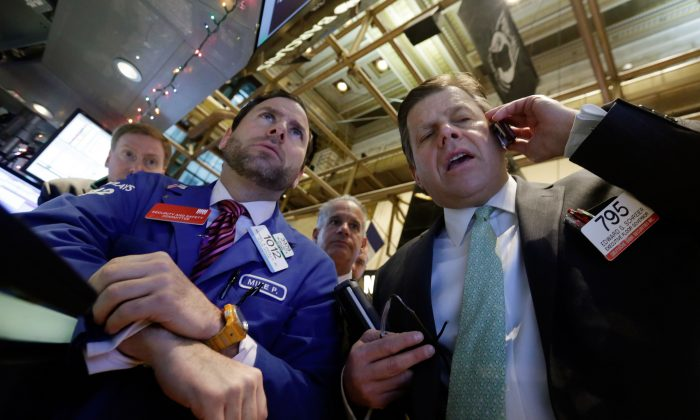 Specialist Michael Pistillo (L) and trader Edward Schreier (R) on the floor of the New York Stock Exchange Tuesday, Jan. 6, 2015. The U.S. stock market is edging higher in early trading as the price of oil extends its slump. (AP Photo/Richard Drew)