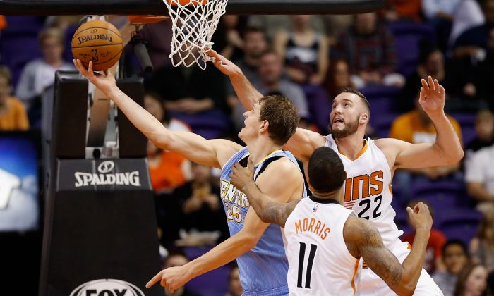 Timofey Mozgov #25 of the Denver Nuggets lays up a shot past Miles Plumlee #22 and Markieff Morris #11 of the Phoenix Suns during the second half of the NBA game at US Airways Center on November 26, 2014 in Phoenix, Arizona. (Photo by Christian Petersen/Getty Images)