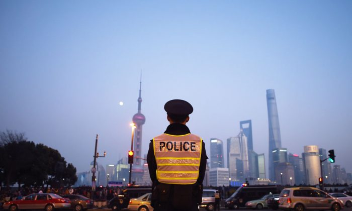 A police officer stands guard at the site of the New Year's Eve stampede in Shanghai, on Jan. 3, 2015. Shanghai authorities have tightened censorship over the incident by blocking online criticism, summoning Internet users, and suppressing the press. (Wang Zhao/AFP/Getty Images)