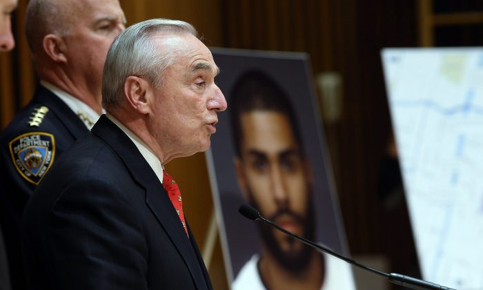 NYPD commissioner William Bratton (R) holds a news conference near a picture of suspect Jason Polanco, after two police officers were shot in the Bronx, New York, on Jan. 6, 2015. (Spencer Platt/Getty Images)
