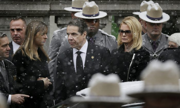New York Gov. Andrew Cuomo (C) waits with his girlfriend, Sandra Lee, while the body of his father, Mario Cuomo, is carried into Church of St. Ignatius Loyola for his funeral in New York, Tuesday, Jan. 6, 2015. Cuomo, 82, died in his Manhattan home on Jan. 1, hours after his son was inaugurated for a second term. (AP Photo/Seth Wenig)