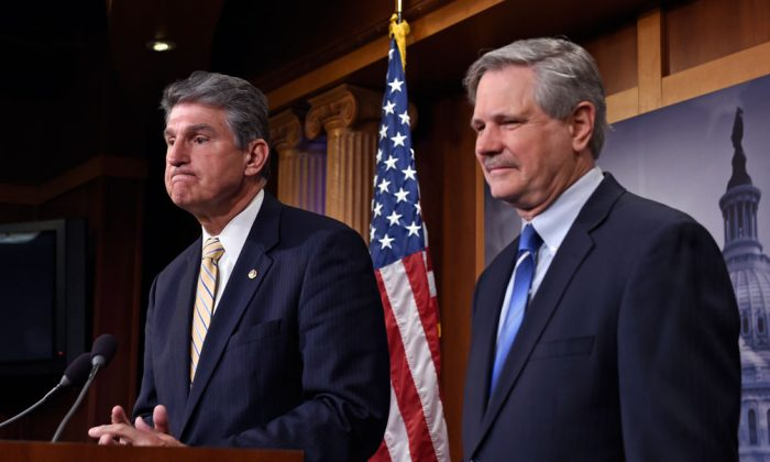 Sen. John Hoeven (R-N.D.) listens at right as Sen. Joe Manchin (D-W.Va.) speaks during a news conference on Capitol Hill in Washington, Jan. 6, 2015, where they discussed their plan to introduce legislation to approve the Keystone XL pipeline project. (AP Photo/Susan Walsh)
