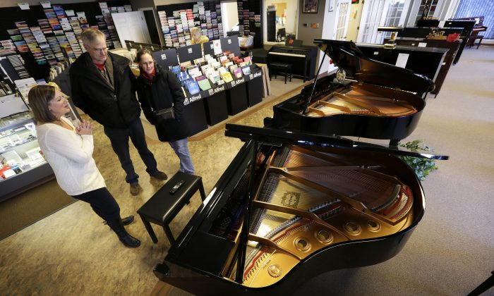 Christi Foster Nunnally (L) shows a grand piano to customers Al and Jill Jorgensen in the Foster Family Music Center piano store showroom in Bettendorf, Iowa on Dec. 10, 2014. The number of stores dedicated to selling pianos is dwindling across the country. (AP Photo/Charlie Neibergall)