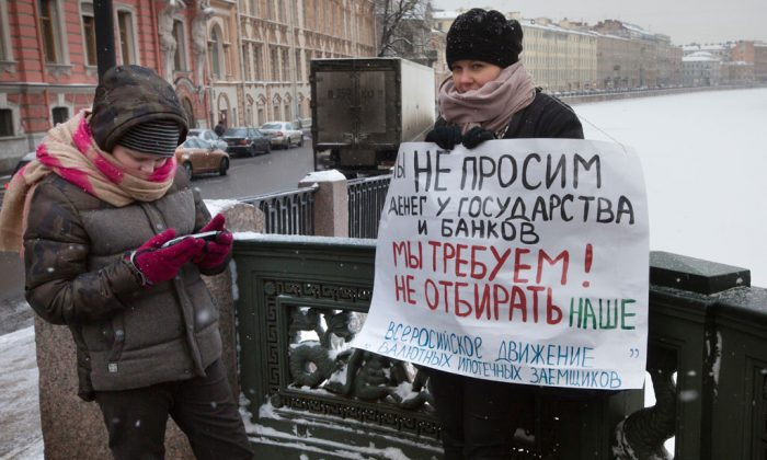 """Oksana Li (R) stands with her son Gleb, 12, in a one-person picket, holding a poster reading """"We are not asking for money from the state and banks, we demand not to take ours!"""" in St.Petersburg, Russia, on Dec. 28, 2014. Oksana went to a one-person picket to protest the onerous foreign currency mortgage that threatens to ultimately deprive thousands of the country's mortgage borrowers of their apartments amid Russia's economic crisis. (AP Photo/Dmitry Lovetsky)"""