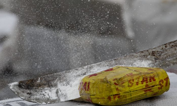 In this file photo, powder flies as an anti-narcotics agent hacks open a package of cocaine. (AP Photo/Arnulfo Franco)