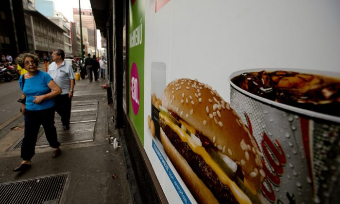 A customer glances at a McDonalds' banner menu showing a burger accompanied by arepas or corn cakes, instead of fries, in Caracas, Venezuela, Tuesday, Jan. 6, 2015. McDonald's franchises in Venezuela have run out of potatoes and are now serving South American alternatives like deep-fried arepas or yuca, a starchy tuberous root. The franchisers are blaming a contract dispute with West Coast dock workers for halting the export of frozen fries to the country. (AP Photo/Fernando Llano)
