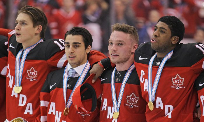"""Canadian junior hockey players (L-R) Jake Virtanen, Robby Fabbri, Max Domi, and Anthony Duclair stand for """"O Canada"""" after winning the gold medal at the Air Canada Centre in Toronto on Jan. 5, 2015. (Claus Andersen/Getty Images)"""