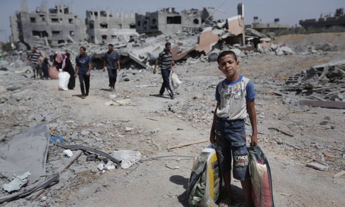 In this Aug. 1, 2014 file photo, Palestinians carry their belongings after salvaging them from their destroyed house in the heavily bombed town of Beit Hanoun, Gaza Strip, close to the Israeli border. (AP Photo/Lefteris Pitarakis)