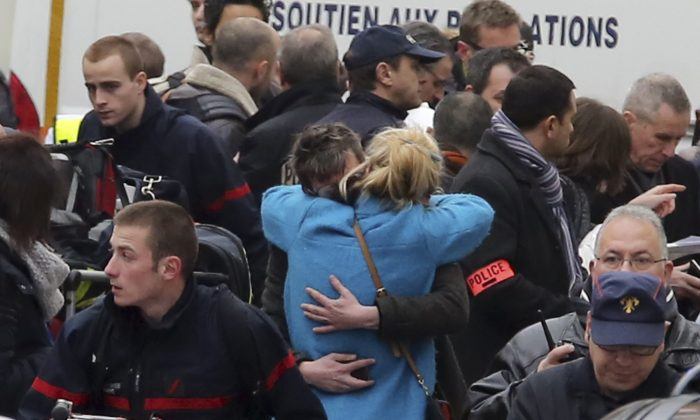 People hug each other outside the French satirical newspaper Charlie Hebdo's office, in Paris, on Jan. 7, 2015. (AP Photo/Remy de la Mauviniere)