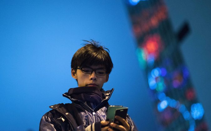 Joshua Wong looks at his mobile phone after addressing protestors at the movement's main protest site in the Admiralty district of Hong Kong on Dec. 6, 2014. (Johannes Eisele/AFP/Getty Images)