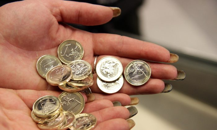 Lithuania became the 19th nation to join the eurozone when it did so on Jan. 1, 2015. A cashier is shown here in Vilnius, Lithuania inspecting euro coins. (Petras Malukas/AFP/Getty Images)