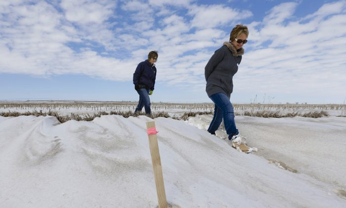 Sisters Jenni Harrington (L) and Abbi Kleinschmidt pass a stake that marks the proposed route of the Keystone XL pipeline on Harrington's property near Bradshaw, Neb., on March 11, 2013. The Republican-led Congress appears ready to approve the Keystone XL oil pipeline but Harrington says they won't sell out the next generation for any amount, not even $50 million. No matter what actions are taken in Washington, the entire 1,179-mile project could be delayed until the state of Nebraska signs off on the route. (AP Photo/Nati Harnik)