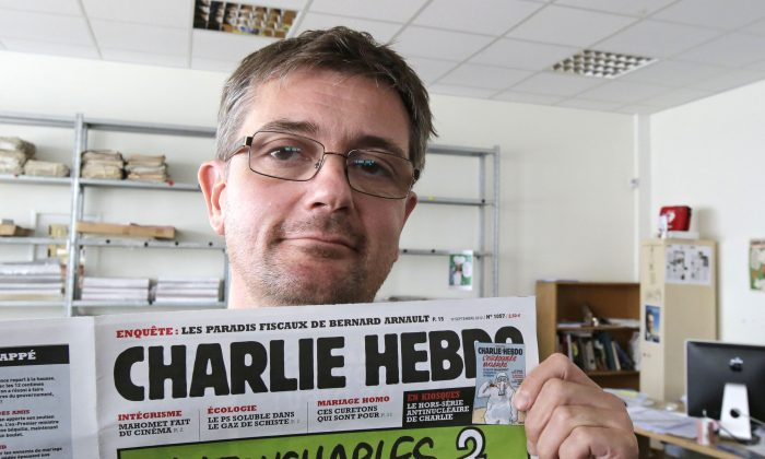 In this Sept.19, 2012 file photo, Stephane Charbonnier also known as Charb, the publishing director of the satirical weekly Charlie Hebdo, displays the front page of the newspaper as he poses for photographers in Paris. (AP Photo/Michel Euler, File)