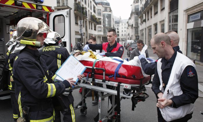 An injured person is carried into an ambulance after a shooting, at the French satirical newspaper Charlie Hebdo's office, in Paris, Wednesday, Jan. 7, 2015. Masked gunmen stormed the offices of a French satirical newspaper Wednesday, killing at least 11 people before escaping, police and a witness said. The weekly has previously drawn condemnation from Muslims. (AP Photo/Thibault Camus)