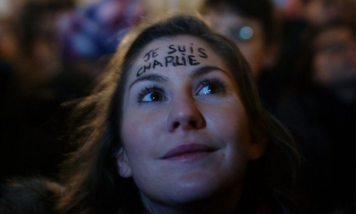 "The inscription ""I am Charlie"" is written on the fronthead of a woman as she attends a gathering to pay respect for the victims of a terror attack against a satirical newspaper, in Paris, France, Wednesday, Jan. 7, 2015. Masked gunmen shouting ""Allahu akbar!"" stormed the Paris offices of a satirical newspaper Wednesday, killing 12 people, including the paper's editor, before escaping in a getaway car. It was France's deadliest terror attack in living memory. (AP Photo/Thibault Camus)"