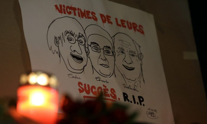 """A drawing depicting cartoonist Jean Cabut (L), Charlie Hebdo editor Stephane Charbonnier (C), and cartoonist Georges Wolinski, all three of whom were killed when masked gunmen stormed the Paris offices of a weekly newspaper Charlie Hebdo and reading in French, """"Victims of their success, R.I.P"""", is placed outside the French Embassy as people gather to express solidarity with victims of the attack in Berlin, Germany, Wednesday, Jan. 7, 2015. Three masked gunmen shouting """"Allahu akbar!"""" stormed the Paris offices of a satirical newspaper Wednesday, killing 12 people, including its editor, before escaping in a car. It was France's deadliest postwar terrorist attack. (AP Photo/Michael Sohn)"""