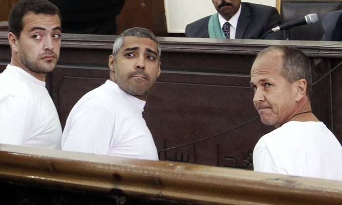 "(L-R) Al-Jazeera journalists Baher Mohamed, Mohammed Fahmy, and Peter Greste appear in court during their trial on terror charges in Cairo on March 31, 2014. Fahmy's family says they have requested his deportation and were told by a senior official the process is in its ""final stages."" (AP Photo/Heba Elkholy, El Shorouk)"
