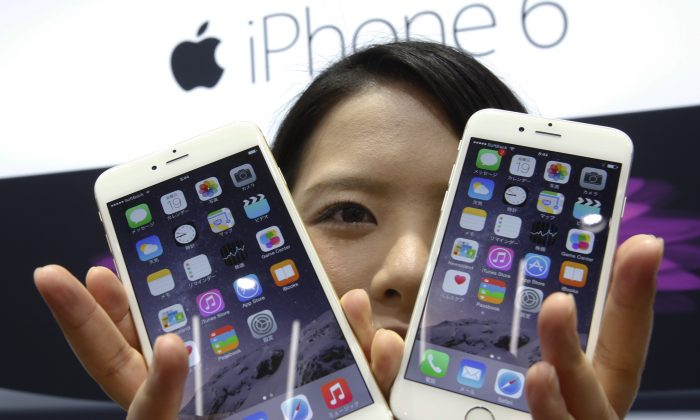 In this Sept. 19, 2014 file photo, a customer shows off the new Apple iPhone 6 and 6 Plus. (AP Photo/Shizuo Kambayashi, File)
