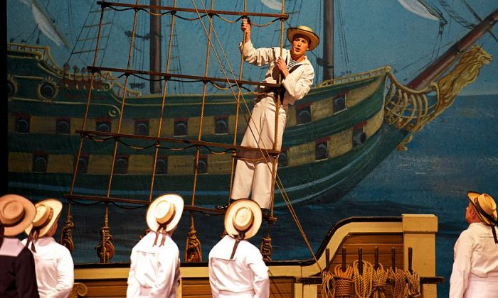"""Cameron Smith as Ralph Rackstraw (played by Daniel Greenwood in the reviewed production) and a chorus of sailors in the New York Gilbert & Sullivan Players production of """"H.M.S. Pinafore."""" (William Reynolds)"""