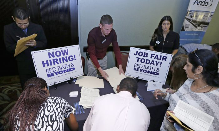 Job seekers fill out a job applications at a Bed Bath and Beyond table at a job fair in Miami Lakes, Fla., on Oct. 22, 2014. (AP Photo/Alan Diaz)